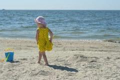 Meisje in een gele kleding op het strand Royalty-vrije Stock Fotografie