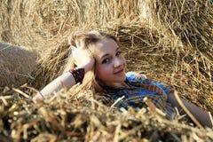 Meisje in een gele stapel van hooi Stock Fotografie