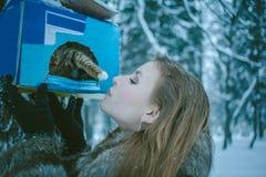 Meisje in een grijze laag en een katje dat haar poot van het vogelhuis raakt stock foto
