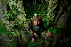 Meisje in een groen jasje met blond haar dichtbij een kunstmatige rots met een grot Fabelachtige fotospruit in de Studio royalty-vrije stock foto's