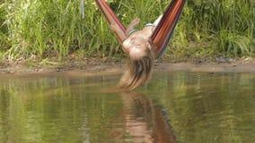 Meisje in een hangmat boven de rivier liggen, en haar haar die in water stock footage