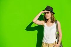 meisje in een hoed op een achtergrond van groene muur Stock Afbeeldingen