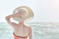 Meisje in een hoed tegen overzees Op de rug is geschilderde zon stock afbeelding