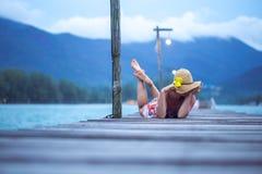 Meisje in een hoedenzitting op een lange houten pijler in de avond Royalty-vrije Stock Foto's