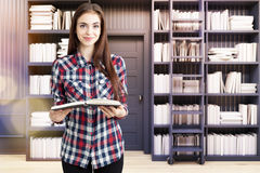 Meisje in een huisbibliotheek met een zwarte ladder, Stock Foto