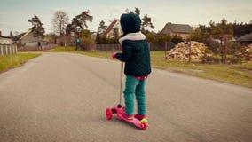 Meisje in een jasje die een autoped berijden op een landweg stock video