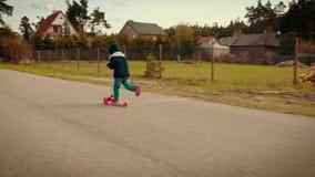 Meisje in een jasje die een autoped berijden op een landweg stock videobeelden