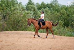 Meisje - een jockey bij het berijden van paard stock foto's