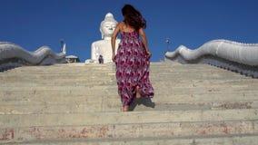 Meisje in een kleding die blootvoets op de stappen lopen Hij stijgt naar grote Boedha Het haar en de kleding ontwikkelen zich stock videobeelden