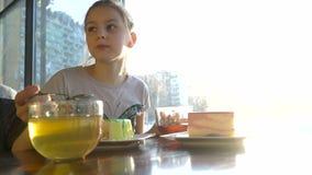 Meisje in een koffie die snoepjes eten stock footage