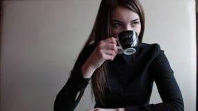 Meisje in een koffie het drinken koffie en het kijken uit het venster stock videobeelden