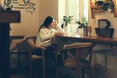 Meisje in een koffiewinkel door het venster royalty-vrije stock afbeelding