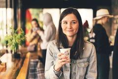 Meisje in een koffiewinkel met een kop van koffie stock foto's