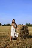 Meisje in een landelijke kleding die zich dichtbij hooiberg bevindt Stock Fotografie