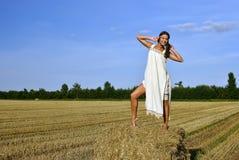 Meisje in een landelijke kleding die zich op de hooiberg bevindt Stock Foto