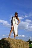 Meisje in een landelijke kleding die zich op de hooiberg bevindt Stock Fotografie