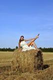 Meisje in een landelijke kledingszitting op de hooiberg Stock Foto's