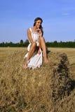 Meisje in een landelijke kledingszitting op de hooiberg Stock Afbeelding