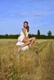 Meisje in een landelijke kledingszitting op de hooiberg Royalty-vrije Stock Fotografie