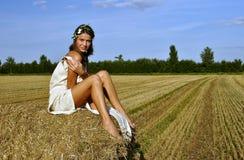 Meisje in een landelijke kledingszitting op de hooiberg Stock Fotografie