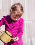 Meisje in een lavendelkleding met een gele geëmailleerde theepot Royalty-vrije Stock Foto's