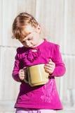 Meisje in een lavendelkleding met een gele geëmailleerde theepot Royalty-vrije Stock Fotografie