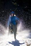 Meisje in een matroos met kap het schoppen sneeuw op een zonnige dag stock fotografie