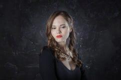 Meisje in een mijmerijstemming De stijlvrouw die van de Noirfilm in kleding zwarte pen in haar hand houden Het schot van de studi Royalty-vrije Stock Afbeelding