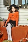 Meisje in een oranje sweater en hoed in Halloween-heks Stock Foto