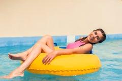 Meisje in een poolzitting in een rubber opblaasbare vlotter royalty-vrije stock afbeeldingen