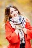 Meisje in een rode laag en sjaal de herfstdag in aard Royalty-vrije Stock Foto's