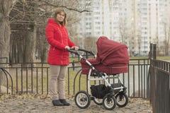 Meisje in een rood jasje met een wandelwagen Royalty-vrije Stock Foto