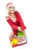 Meisje in een santahoed met de giften van Kerstmis stock fotografie