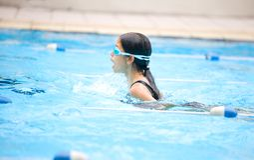 Meisje in een school die comp zwemt Stock Afbeelding