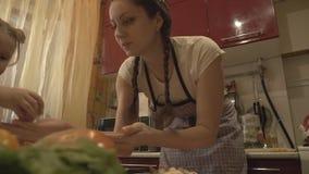 Meisje in een schort die een huis-gekookte maaltijd in de keuken voorbereiden stock video