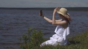 Meisje in een strohoed die fotograferen op een mobiele telefoon Mooie jonge vrouw die bij de rivier wordt gefotografeerd stock footage