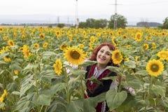 Meisje in een traditionele Bulgaarse kleding op een gebied van zonnebloemen royalty-vrije stock foto