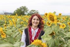 Meisje in een traditionele Bulgaarse kleding op een gebied van zonnebloemen royalty-vrije stock fotografie