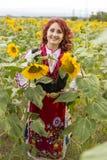 Meisje in een traditionele Bulgaarse kleding op een gebied van zonnebloemen stock fotografie