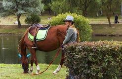 Meisje in een van het cowboyhoed en paard het knagen aan gras Stock Afbeelding
