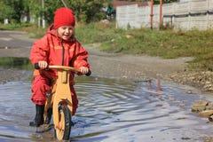 Meisje in een vulklei op een houten fiets Royalty-vrije Stock Afbeeldingen
