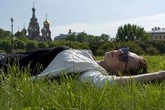 Meisje in een wit jasje en zonnebril die op het gras op liggen stock afbeeldingen