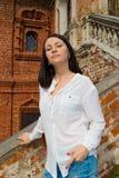Meisje in een witte blouse die zich op steentreden bevinden Stock Afbeelding