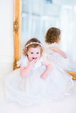 Meisje in een witte kleding naast een spiegel Stock Foto's