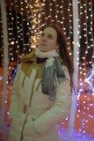 Meisje in een witte laag in de winter en gloeiende Kerstmisslinger stock afbeeldingen