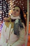 Meisje in een witte laag in de winter en gloeiende Kerstmisslinger stock foto