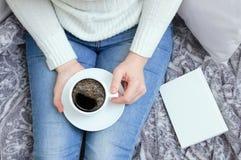 Meisje in een witte sweater en jeans op laag met een kop van koffie in handen royalty-vrije stock foto