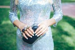 Meisje in een zilveren kleding met gewrichten van een de kleine zwarte handtasmessing Geplaatste de toebehoren van manierkleren M royalty-vrije stock foto