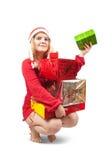 Meisje in een zitting van de santahoed met de giften van Kerstmis stock afbeeldingen