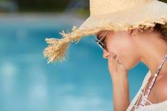 Meisje in een zonhoed daarna de pool stock afbeelding